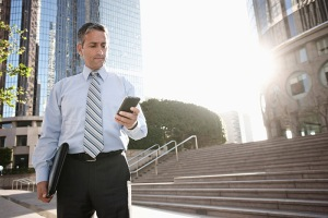 Hispanic businessman text messaging on cell phone outdoors